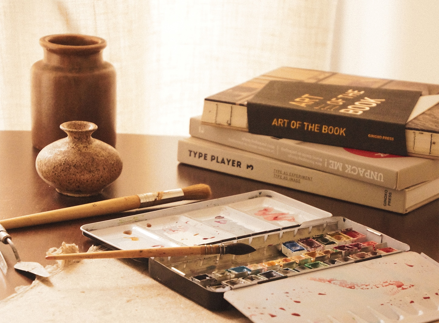 Palette d'aquarelle avec des éléments naturels, des livres de design graphique et de la peinture